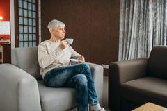 Erwachsener Mann trinkt Kaffee und Lesezeitung lizenzfreie stockbilder