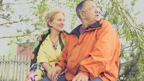Erwachsener Mann und Frau, die in einem Park auf einer Bank, weg schauend sitzt und sprechen Langsame Bewegung 1920x1080 HD stock footage