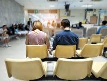 Erwachsener Mann und Frau sitzen auf der gelben rostfreien medizinischen Stuhlaufwartung und den Gesundheitsdiensten zum Krankenh lizenzfreie stockbilder