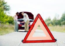 Erwachsener Mann und Frauen nähern sich defektem Auto Stockbilder