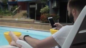 Erwachsener Mann verzeichnet den Schirm seines Smartphone nahe dem Swimmingpool in einer Liste stock video