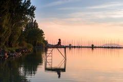 Erwachsener Mann in Yogaposition auf dem Pier Stockfotos