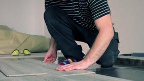 Erwachsener Mannesarbeitskraft, die Laminatboden, sich hin- und herbewegenden Bretterboden installiert stock footage