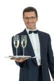 Erwachsener Manneskellner, der zwei Glas Champagner lokalisiert dient Lizenzfreie Stockfotos