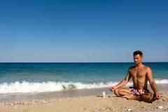 Erwachsener Mannesmeditationspraxis morgens auf dem Strand Stockbild