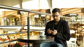 Erwachsener Mannestrinkender Kaffee mit einem Telefon in seiner Hand in den Cafés stock footage