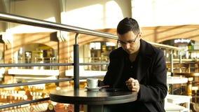 Erwachsener Mannestrinkender Kaffee mit einem Telefon in seiner Hand in den Cafés stock video