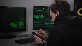 Erwachsener Mannhacker, mit Stoppel auf seinem Gesicht, eine Schwarzsportjacke tragend sitzt in einem geheimen Bunker und macht C stock video