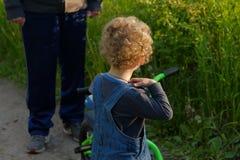 Erwachsener Mannmann schilt kleinen gelockten blonden Jungen mit wenigem Fahrrad stockfoto
