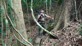 Erwachsener Mannphotograph, der durch schönen Dschungel geht stock video footage
