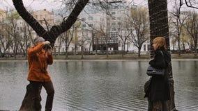 Erwachsener Mannphotograph machen Fotos einer Frau mit alter Weinlesefilmkamera stock footage