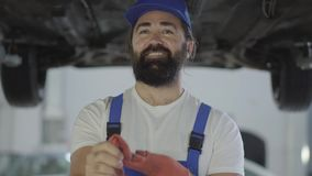 Erwachsener Mechaniker schaut auf Autounterseite, dann nimmt Handschuhe heraus Positive Arbeitskraft steht unter dem angehobenen  stock video footage