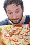 Erwachsener mit überraschtem Gesicht auf Pizzatabelle stockbild