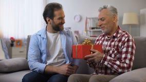 Erwachsener Sohn, der ?lteren Vati mit dem Vatertag, Geburtstag feiernd, Sorgfalt begl?ckw?nscht stock video footage