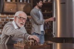 erwachsener Sohn, der im Kühlschrank und in älterem Vater spielen Schach schaut lizenzfreie stockfotos