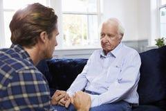 Erwachsener Sohn, der mit deprimiertem Vater At Home spricht lizenzfreie stockbilder