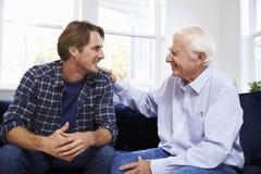 Erwachsener Sohn, der zu Hause auf Sofa And Talking To Father sitzt stockbild