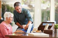 Erwachsener Sohn-helfende Mutter mit Laptop stockbilder