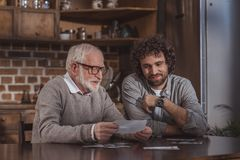 erwachsener Sohn und älterer Vater, die alte Fotos betrachtet lizenzfreies stockbild