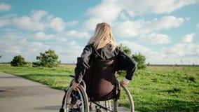 Erwachsener sperrte Frau fährt ihren Rollstuhl im Parkbereich am sonnigen Tag stock video footage
