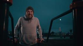 Erwachsener Sportler bildet im Yard der Stadt am dunklen Abend aus und hebt auf Hände an stock footage