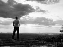 Erwachsener Sportler im grauen Hemd auf der Klippe in den felsigen Bergen parken und passen in Landschaft auf Stockfoto