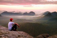 Erwachsener Sportler im weißen Hemd, in den dunklen trousars und in der roten Kappe Mann des kurzen Haares des Ingwers sitzen auf Stockfoto