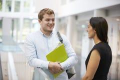 Erwachsener Student und Lehrer, die im Hochschulfoyer spricht lizenzfreies stockfoto