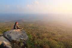 Erwachsener Tourist in der schwarzen Hose, Jacke und dunkle Kappe sitzen auf dem Rand der Klippe und dem Schauen des nebelhaften  stockfoto