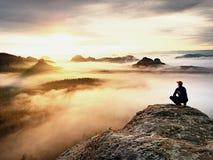 Erwachsener Tourist in der schwarzen Hose, Jacke und dunkle Kappe sitzen auf Klippe ` s Rand und dem Schauen zum nebelhaften hüge stockfoto