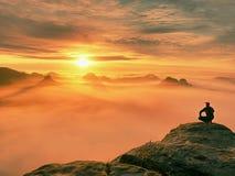 Erwachsener Tourist in der schwarzen Hose, Jacke und dunkle Kappe sitzen auf Klippe ` s Rand und dem Schauen zum nebelhaften hüge lizenzfreies stockbild