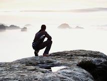 Erwachsener Tourist in der schwarzen Hose, Jacke und dunkle Kappe sitzen auf Klippe ` s Rand und dem Schauen zum nebelhaften hüge lizenzfreie stockfotos