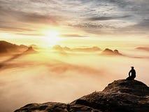 Erwachsener Tourist in der schwarzen Hose, Jacke und dunkle Kappe sitzen auf Klippe ` s Rand und dem Schauen zum nebelhaften hüge lizenzfreie stockfotografie