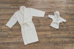 Erwachsener und Kinder` s weiße Roben, die auf hölzernem Hintergrund liegen Stockbilder