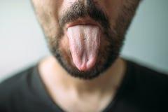 Erwachsener unrasierter Mann, der heraus Zunge haftet stockbild