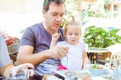 Erwachsener Vater, der seine nette Kleinkindtochter während des Familienfrühstücks im äußeren Café einzieht Familienrest, Zeit co lizenzfreie stockfotos