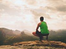 Erwachsener Wanderer in den schwarzen kurzen Hosen und grünes Unterhemd sitzen auf Gebirgsrand Mann, der Ansicht genießt lizenzfreies stockbild