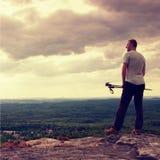 Erwachsener Wanderer mit Pfosten in der Hand Wanderer machen eine Pause auf felsigem Standpunkt über Tal Sonniger Tagesfelsige Be Stockfotografie
