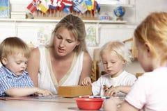 Erwachsener, welche jungen Kindern bei Montessori/bei Pre-Sch hilft lizenzfreies stockfoto