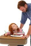 Erwachsenes helfendes Schulkind am Schreibtisch Stockbilder