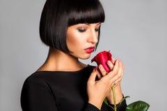 Erwachsenes Mädchen der Schönheit mit der Rotrose, die unten schaut stockfotografie