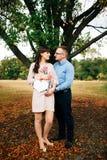 Erwartung das schwangere glückliche Paar, das in Form leeres Holzkohlenbrett des Herzens hält Stockfotos