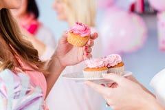 Erwartung der Mutter, die kleinen Kuchen auf Babypartypartei isst Stockfotos