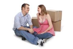 Erwartung der Paare, die nahe beweglichen Kästen sitzen stockbild