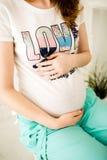 Erwartungsvolle junge Mutter hält schwangeren Bauch Stockfotos