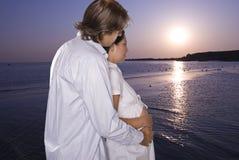 Erwartungsvolle Paare auf dem Strand, der Sonnenaufgang betrachtet Stockfoto