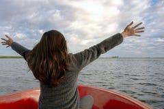 Erweiterungsarme der Frau und auf dem Boot und dem Schauen vorwärts in Lagune genießen stockbilder