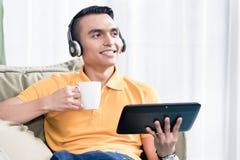Erwogener Mann, der Kaffeetasse und digitale Tablette hält stockbild