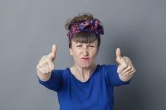 Erzürnte Frau, die mit den Daumen oben für kämpfenden Erfolg die Stirn runzelt Lizenzfreie Stockfotos