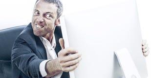 Erzürnter Geschäftsmann mit den ausbauchenden Augen und Zähnen, die Computer halten stockfoto